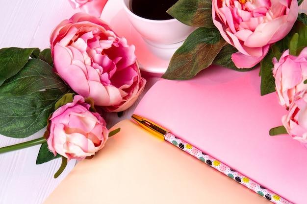 Zbliżenie kwiatów róży z piórem i filiżanką kawy. otwórz różowy notatnik i ołówek.