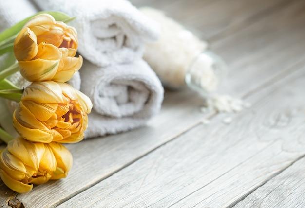 Zbliżenie kwiatów z akcesoriami do kąpieli na niewyraźne tło. pojęcie zdrowia i urody.
