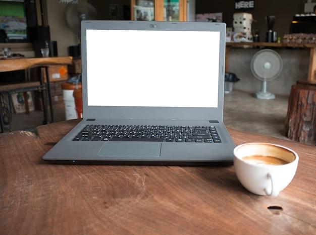 Zbliżenie labtop komputer z pustym pokazem w sklep z kawą pojęcia imege robić reklamuje produkt