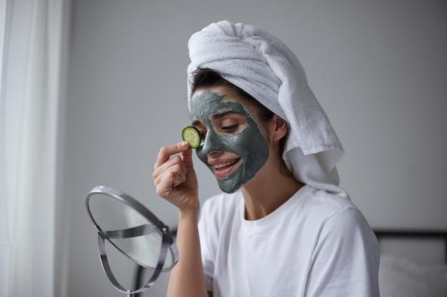 Zbliżenie: ładna młoda brunetka kobieta z ręcznikiem na głowie kładzie świeży ogórek na oku podczas zabiegu kosmetycznego wczesnym rankiem, siedząc nad wnętrzem domu