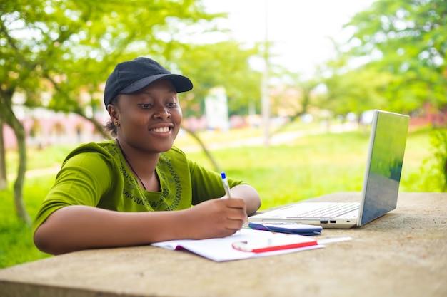 Zbliżenie ładnej afrykańskiej studentki, która czuje się podekscytowana, gdy pracuje nad swoim zadaniem w kampusie