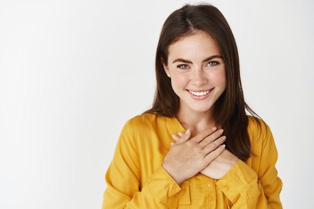 Zbliżenie ładnej kobiety, która dziękuje, trzyma ręce na sercu i uśmiecha się zachwycona, stojąc nad białą ścianą