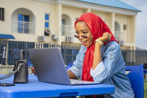 Zbliżenie ładnej młodej kobiety afroamerykańskiej patrzącej z podekscytowaniem na ekran swojego laptopa
