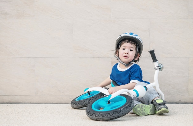 Zbliżenie ładny dzieciak siedzi na marmurowej podłodze i płacze z powodu spadającego roweru na parkingu