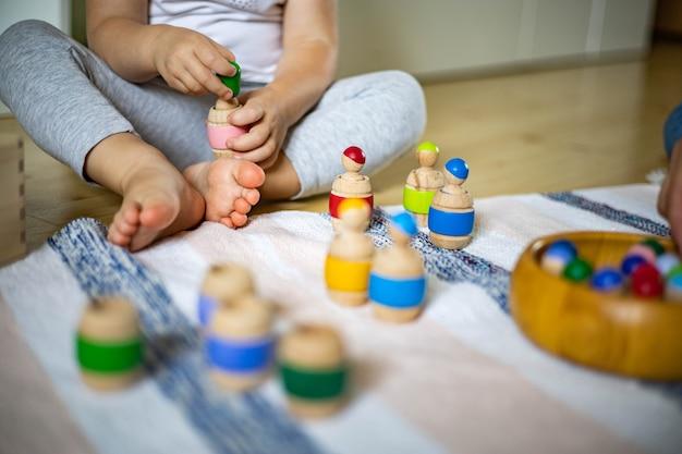 Zbliżenie ładny maluch grający w ekologiczną drewnianą grę edukacyjną wykorzystuje metodę materiałów montessori