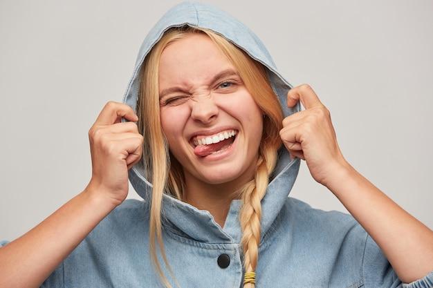 Zbliżenie ładny żartuje piękna blondynka młoda kobieta z warkoczem, ręce trzymają kaptur, czuje się szczęśliwy