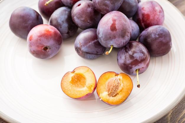 Zbliżenie łamana dojrzała błękitna śliwka i całe jagody na talerzu na woodtable