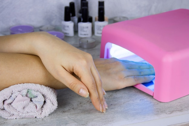 Zbliżenie lampy do rąk i paznokci kobiet suszenia, proces manicure w salonie piękności
