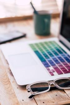 Zbliżenie laptopa z okularami, telefonem i filiżanką z lub kawą na stole z drewna w domu - nikt na zdjęciu - nowoczesna koncepcja modnego miejsca pracy hipster z biurem technologii