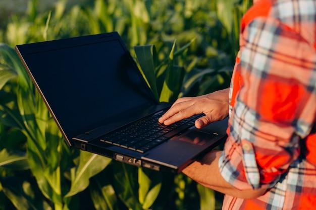 Zbliżenie laptopu ekran w męskie ręki. agronomia stoi w polu gospodarstwa otwarty notatnik