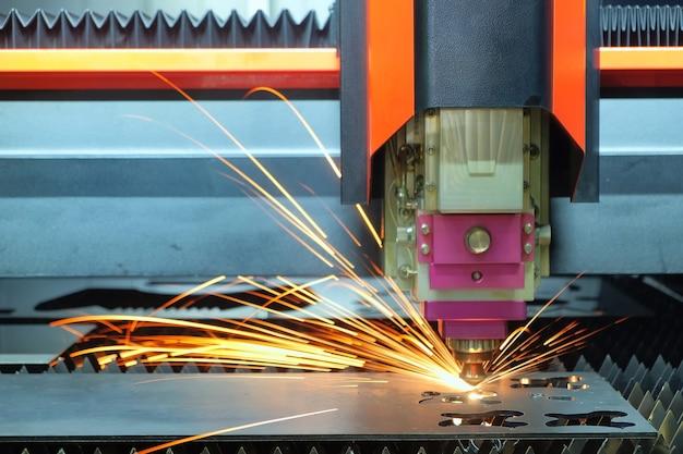 Zbliżenie laserowa maszyna do cięcia pracuje ze stalową płytą, aż iskrzy na inteligentnej fabryce