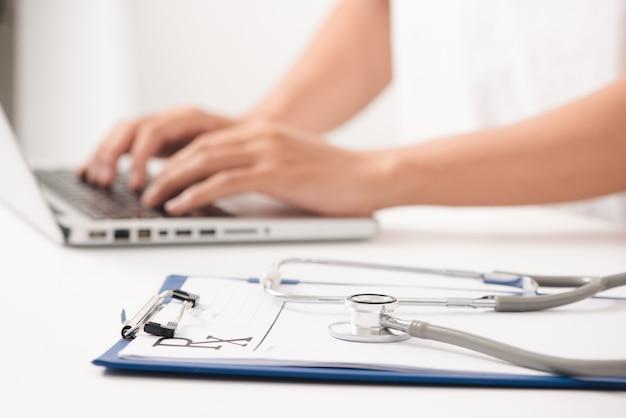 Zbliżenie: lekarka pisząca na komputerze, siedząca przy stole w szpitalu