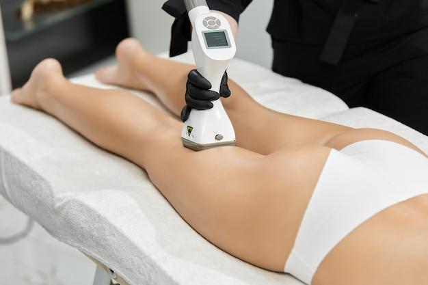 Zbliżenie: lekarz robi masaż kobiecych nóg z masażerem lpg w profesjonalnym salonie