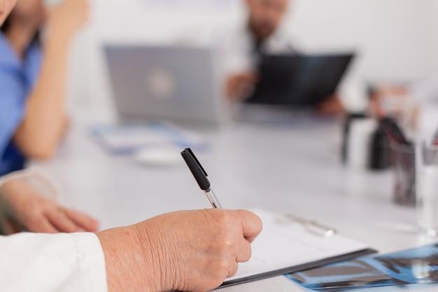 Zbliżenie lekarz starsza kobieta pisze leczenie choroby w schowku przepisując tabletki opieki zdrowotnej leki siedząc przy biurku w sali konferencyjnej