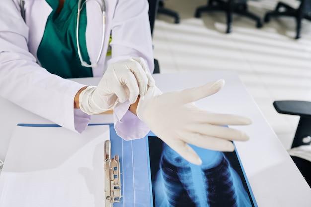 Zbliżenie lekarza pierwszego kontaktu zakładającego gumowe rękawiczki podczas przygotowań do obmacywania pacjenta
