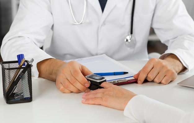 Zbliżenie lekarza przy użyciu pulsoksymetru