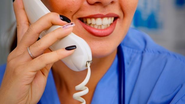 Zbliżenie lekarza specjalisty rozmawiającego przez telefon podczas komunikacji telezdrowia, pomagając pacjentowi z łagodnymi schorzeniami. lekarz w mundurze, asystent lekarza oferujący konsultacje