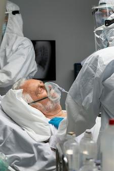 Zbliżenie lekarzy i pacjenta z maską tlenową
