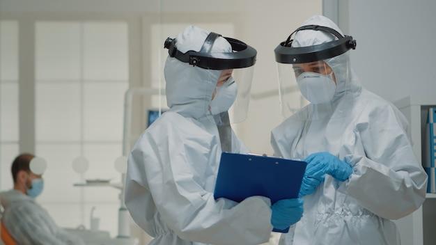 Zbliżenie lekarzy stomatologów rozmawiających w garniturze hazmat