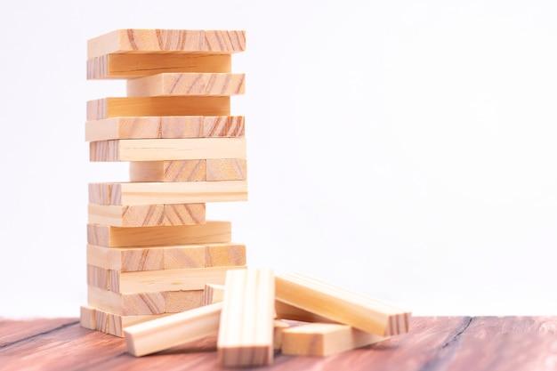 Zbliżenie: lekka drewniana wieża z klocków. gra planszowa na stole. aktywność na rzecz strategii i koncentracji. pomysł na biznes
