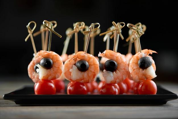 Zbliżenie lekkiej przystawki z restauracji z krewetkami, czarnymi oliwkami i świeżymi pomidorami wiśniowymi. pyszne danie na lekki bufet alkoholowy lub catering z szampanem zdjęcie zostało zrobione na czarnej ścianie