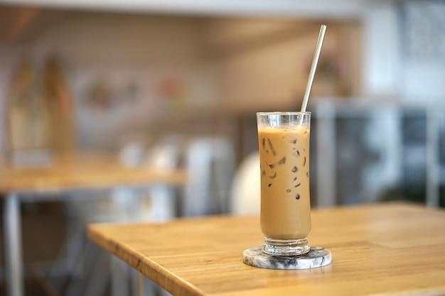 Zbliżenie lodowa kawa z metalową słomą z cukiernianym tłem