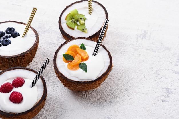 Zbliżenie lody w czterech misach kokosowych z jagodami na białym tle