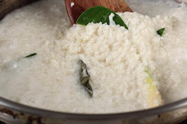 Zbliżenie: łopatka na patelni lepkiego ryżu wrzenia na piecu. przetwarzanie szefa kuchni przygotowującego lepką przekąskę ryżową (lemper) w kuchni