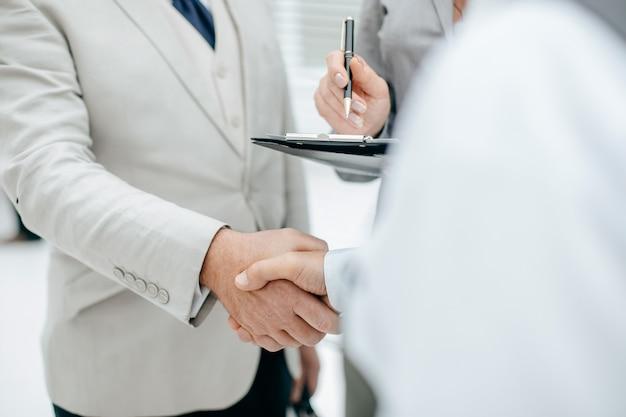 Zbliżenie ludzi biznesu, którzy odnieśli sukces, ściskają ręce w biurze