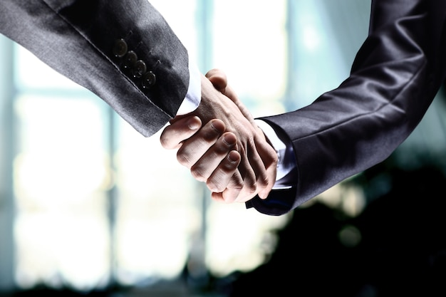 Zbliżenie ludzi biznesu ściskających ręce, aby potwierdzić ich partnerstwo