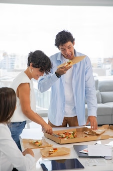 Zbliżenie ludzi jedzących pizzę w pracy