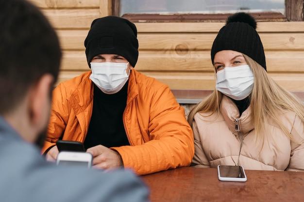 Zbliżenie ludzi noszących maski ochronne