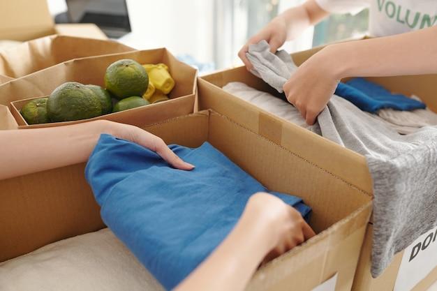 Zbliżenie ludzi pakujących schludne ubrania i świeżą żywność w kartony dla osób dotkniętych klęską żywiołową