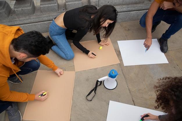 Zbliżenie ludzi piszących na afiszach