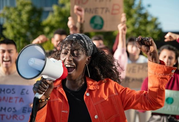 Zbliżenie ludzi protestujących przez megafon