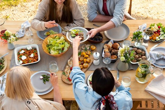 Zbliżenie ludzi przy stole z pysznym jedzeniem