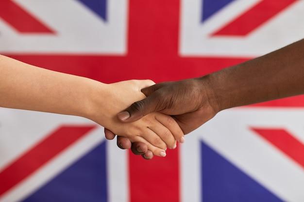 Zbliżenie ludzi ściskających dłonie przeciwko flagi brytyjskiej