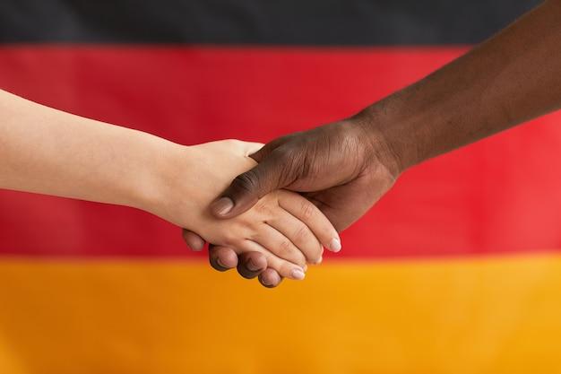 Zbliżenie ludzi ściskających dłonie przeciwko niemieckiej fladze
