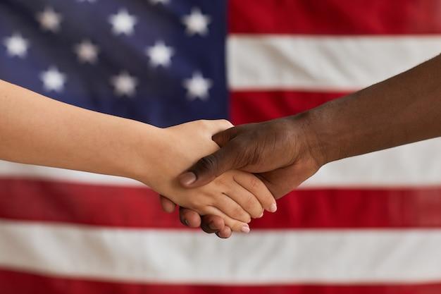 Zbliżenie ludzi ściskających ręce przeciwko amerykańskiej fladze