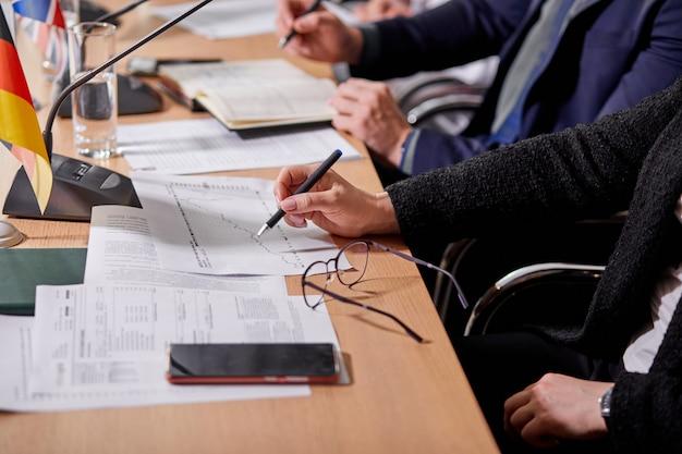 Zbliżenie ludzi siedzących przy biurku, robiąc notatki, dokumenty, konferencja prasowa. spotkanie biznesowe lub polityczne w sali konferencyjnej