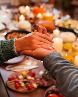 Zbliżenie ludzi trzymających się za ręce podczas kolacji