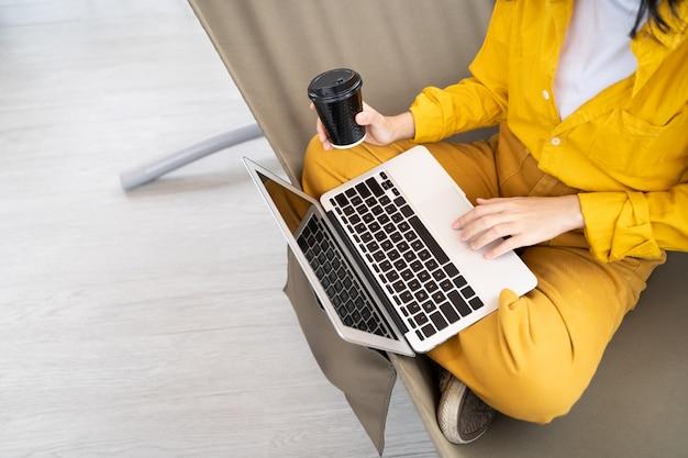 Zbliżenie ludzie używa laptop i pijący kawę