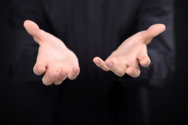 Zbliżenie ludzkich rąk wyciągających się z ciemności