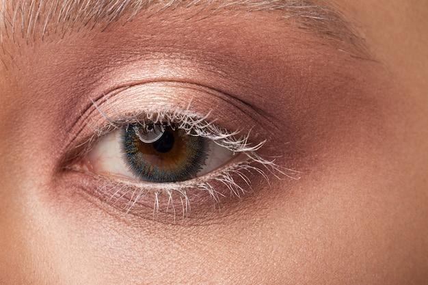 Zbliżenie ludzkiego oka z soczewkami kontaktowymi.