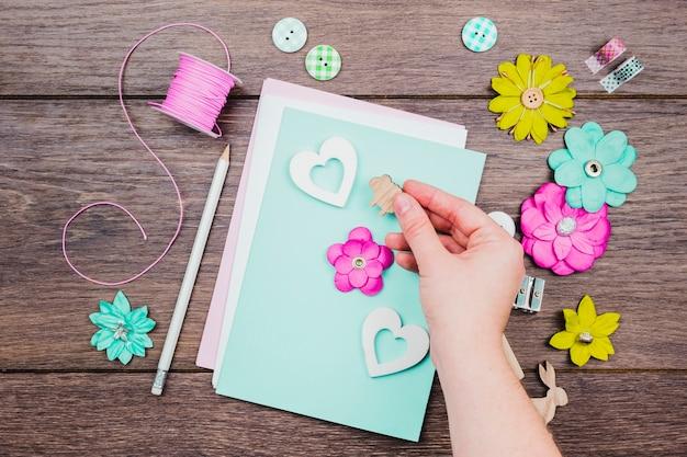 Zbliżenie ludzkiej ręki dekorowanie karty z pozdrowieniami na drewniane biurko