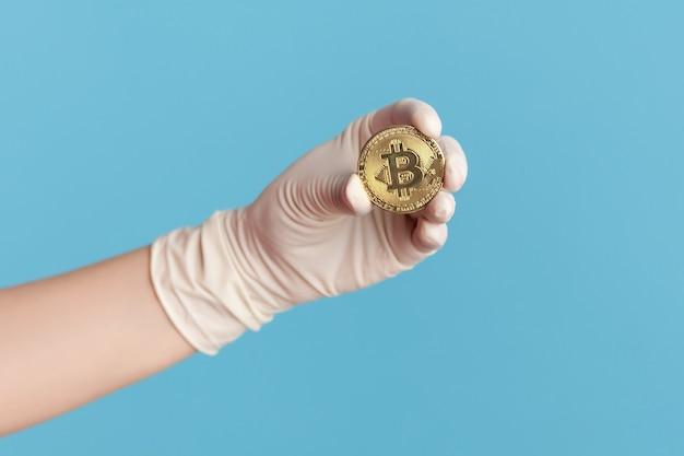 Zbliżenie ludzkiej ręki w białe rękawiczki chirurgiczne, trzymając i pokazując symbol bitcoin w ręku.