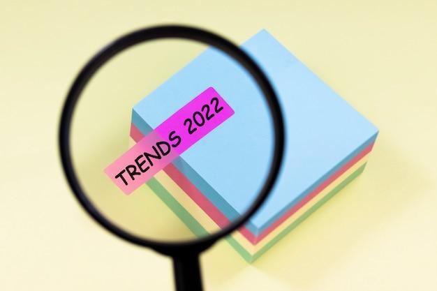 Zbliżenie lupy z tekstem trendy 2022 na różowej naklejce na żółtym tle