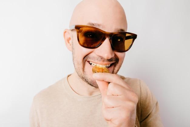 Zbliżenie łysy mężczyzna śmieszny portret. chciwy górnik kryptowaluty gryzie metalowe monety bitcoin, aby sprawdzić autentyczność. sukces obsesji na punkcie pieniędzy biznesmenów
