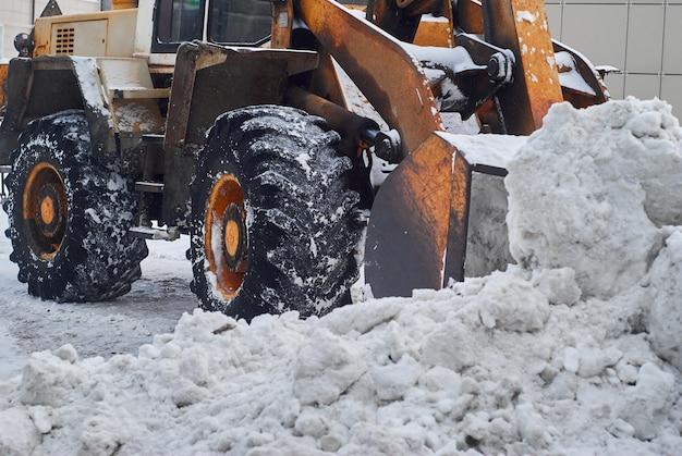 Zbliżenie — łyżka ładowarki usuwa zaspę śnieżną