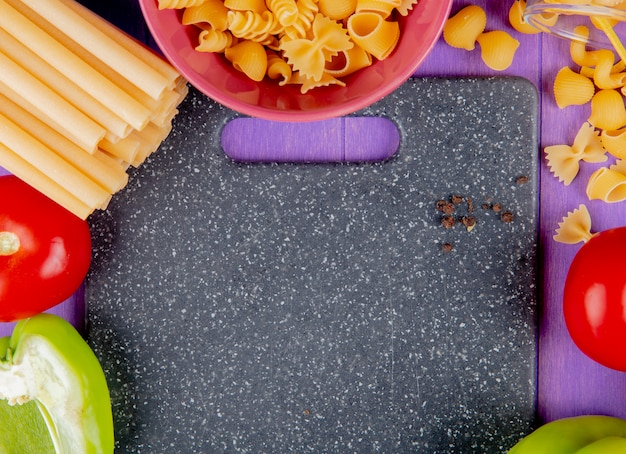 Zbliżenie macaronis jak bucatini rotini i inne z pomidorami pieprz wokół deski do krojenia na fioletowej powierzchni